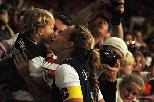 USA captain Christie Rampone greets her two year old daughter Reece and her husband Chris